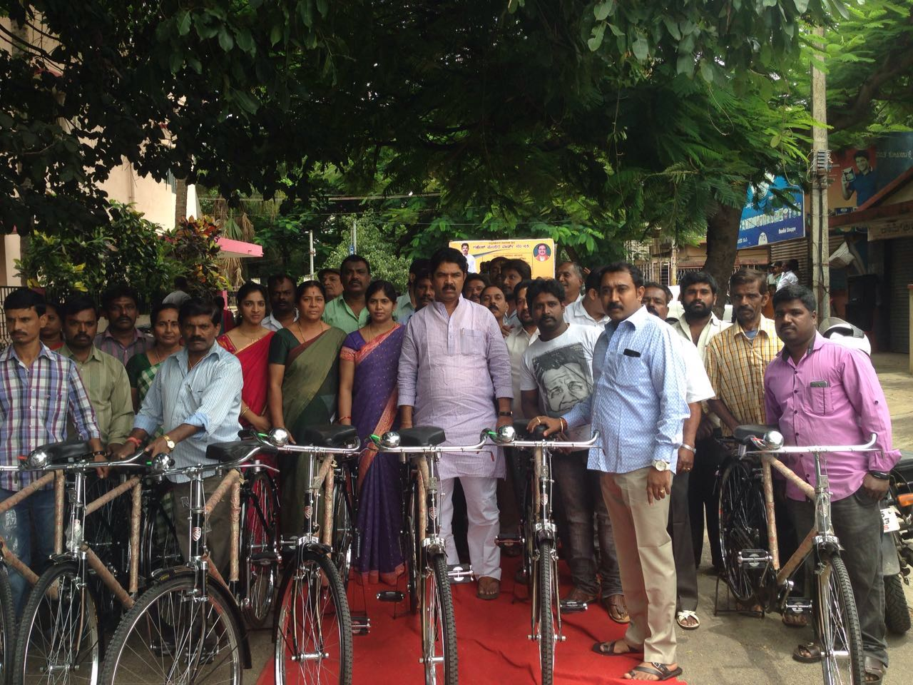 R Ashok distributing bicycles poor residents